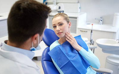 Woman with toothache in dentist's chair, dentist in foreground