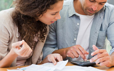 Couple using calculator and looking at bills
